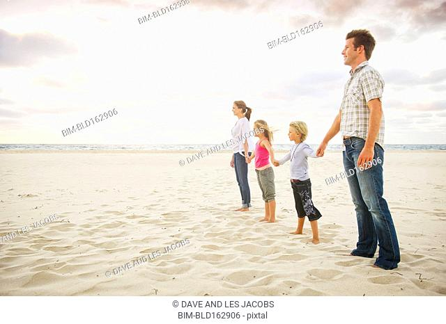 Caucasian parents and children holding hands on beach