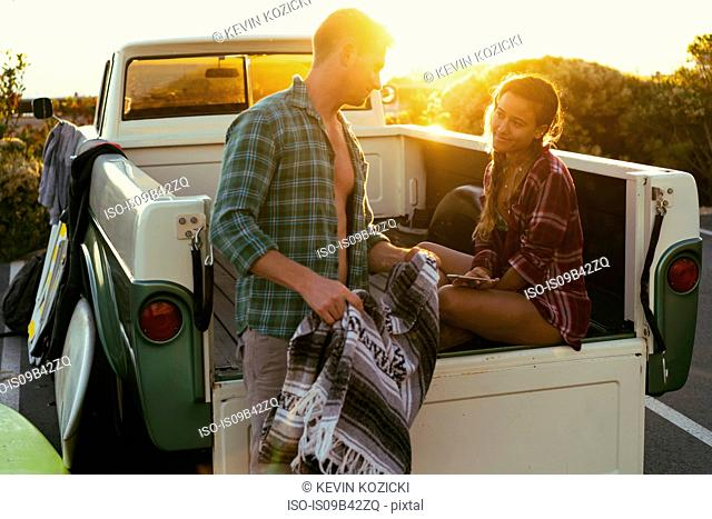 Surfing couple in back of pickup truck at sunset at Newport Beach, California, USA