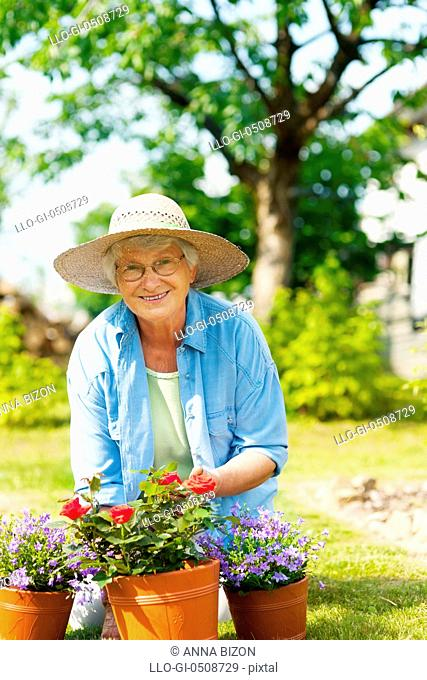 Senior woman with flowers in garden Debica, Poland
