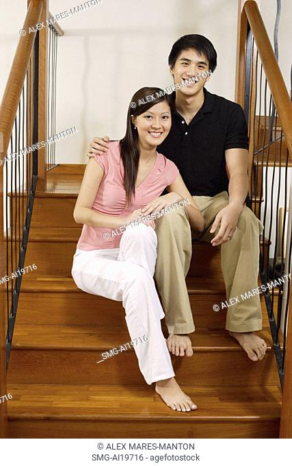Couple sitting on stairs, looking at camera