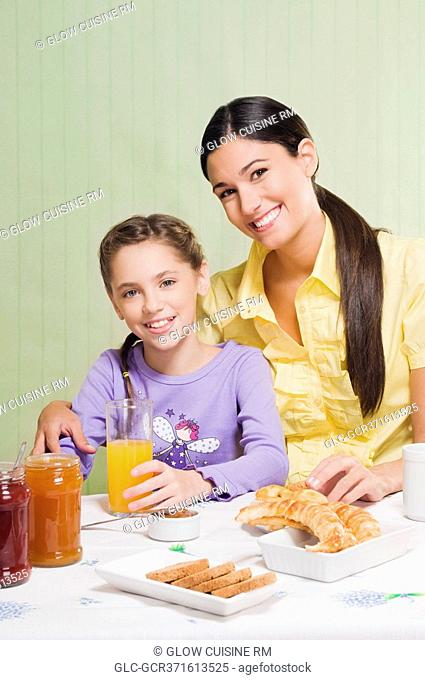 Woman with her daughter at a breakfast table