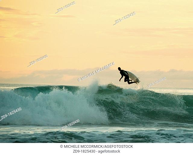A surfer leaps back over a breaking wave in the peach-hued sunset
