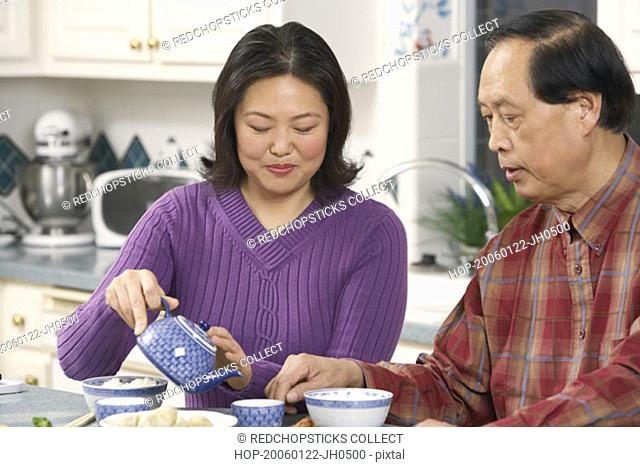 Close-up of a father looking at his daughter pouring tea