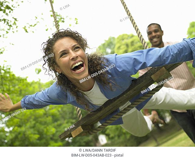 Couple swinging on swing