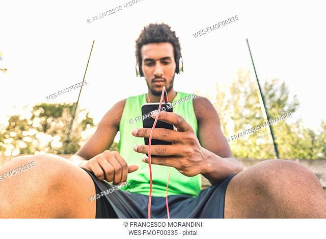 Basketball player listening music, smartphone and headphones