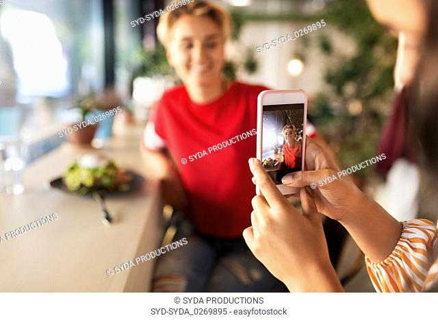 women having lunch and photographing at cafe