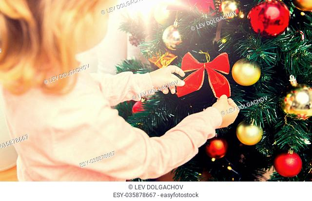 children, christmas, new year, holidays and people concept - close up of little girl decorating christmas tree at home