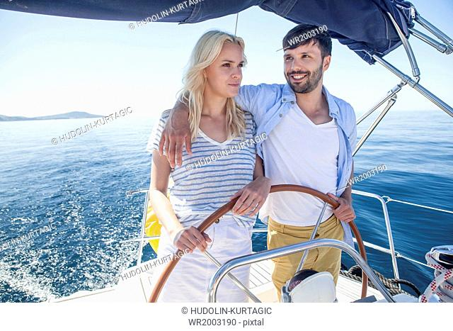 Young couple steering together on sailboat, Adriatic Sea