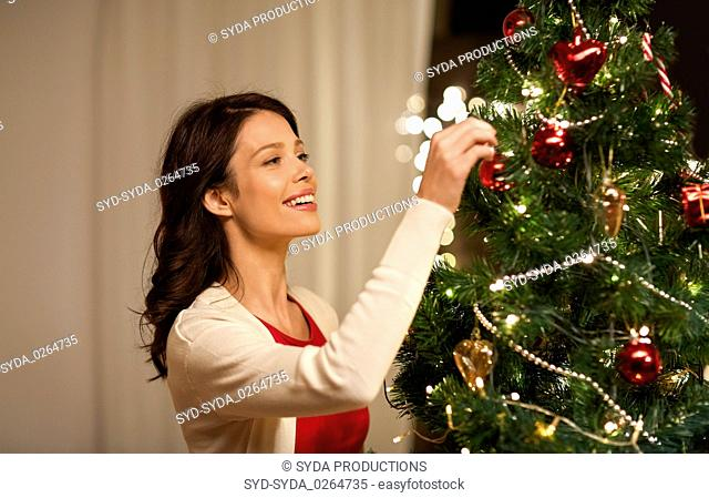 happy woman decorating christmas tree at home