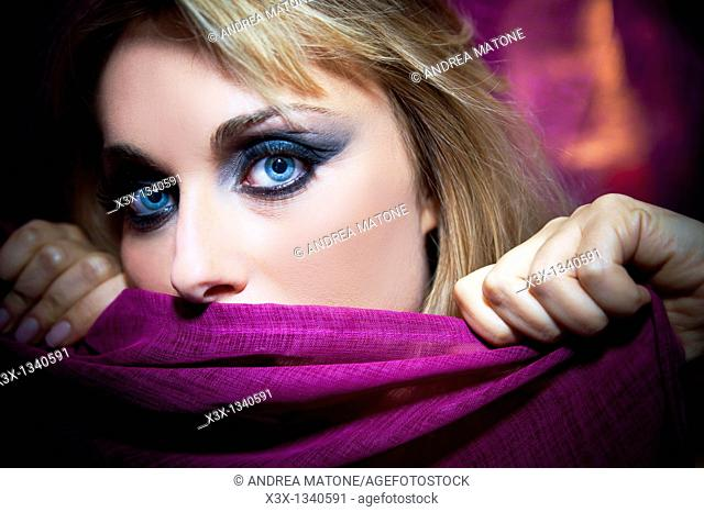 Woman model with makeup holding a purple scarf