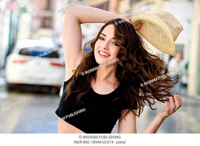 Happy young woman with blue eyes smiling in urban background. Girl wearing summer clothes and sun hat