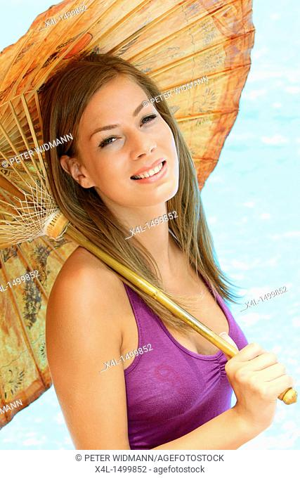 young woman with a parasol on the beach, portrait