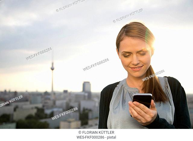 Germany, Berlin, Young woman on rooftop terrace, using mobile phone