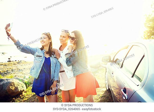 happy women taking selfie near car at seaside
