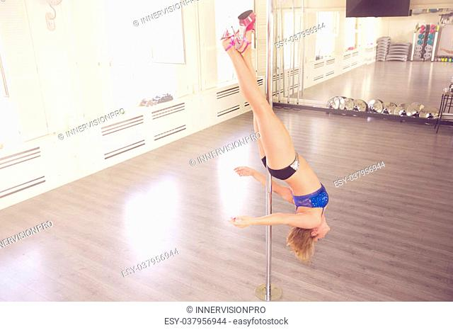 A photo of young woman training on dance pole in vertical position. She's hanging upside down