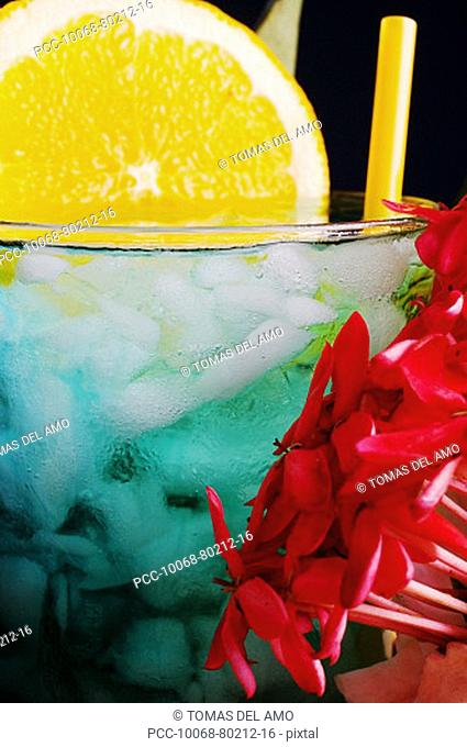 A tropical drink garnished with flowers and fruit