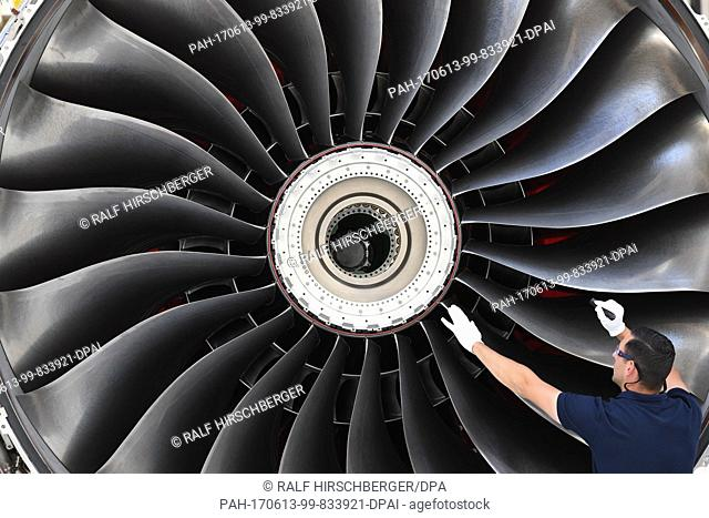 A novel airplane engine of the Rolls-Royce Trent XWB type being inspected by an employee in an assembly hall inDahlewitz, Germany, 12 June 2017