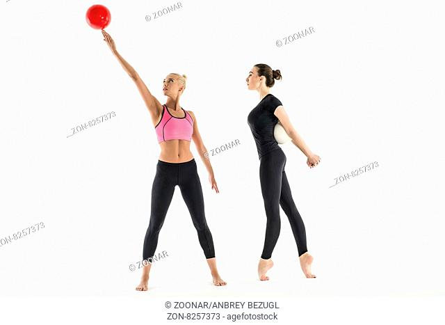 Two sports girl in black leggings. Perform gymnastic exercises with a ball. One stretched on tiptoes prognuv back. Second balances a ball on hand