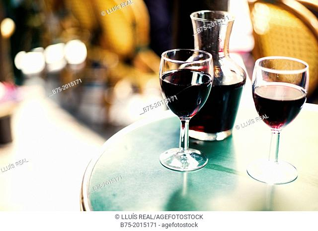 closeup of a bar table with a traditional bottle and two glasses of wine Beaujolais in Paris, France