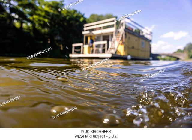 Water surface with house boat in background