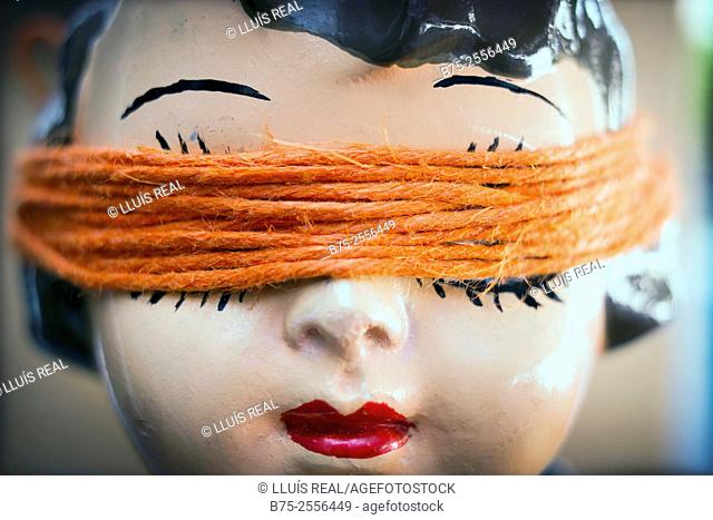 Head of antique porcelain doll with a orange rope covering her eyes