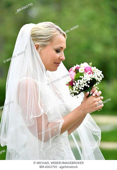 Bride in wedding dress with veil looking at bridal bouqet, Germany