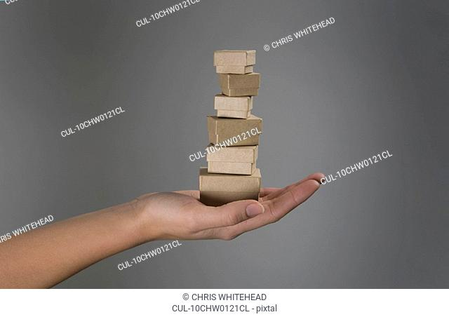 Female hands holding pile of small boxes