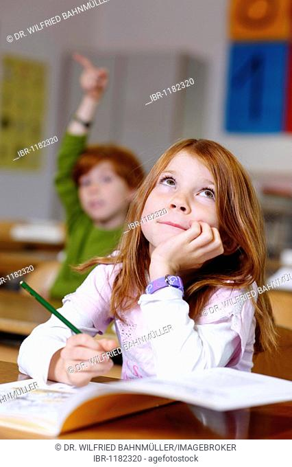 Children in a classroom in primary school, girl looking clever, cunning and knowledgable, equal oppurtunity in the education system