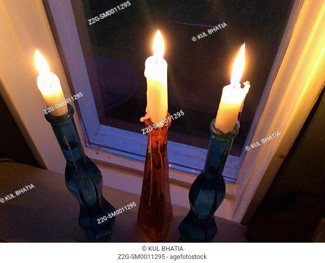 Three candles in a window at dusk, Halifax, Canada