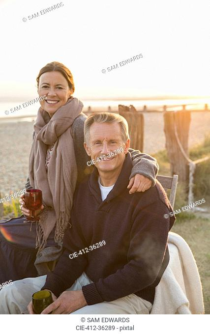 Portrait smiling mature couple drinking wine on sunset beach