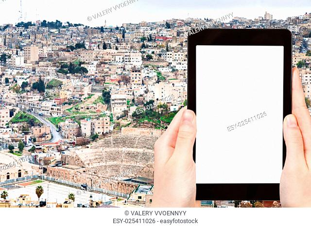 travel concept - tourist photograph skyline of Amman city, Jordan on tablet pc with cut out screen with blank place for advertising logo