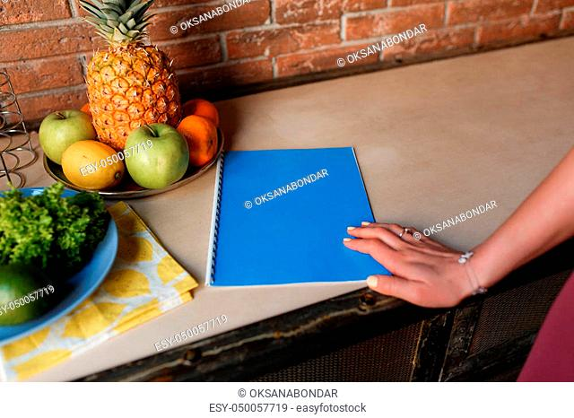Healthy Food. Woman Hand on blue notebook, kitchen table with pineapple and fruit