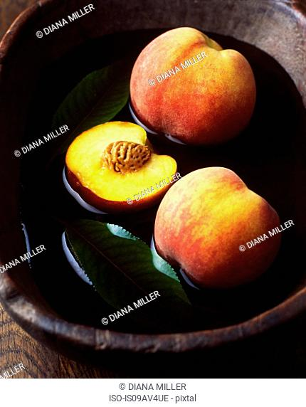 Whole and half peaches and leaves in vintage wooden bowl of water