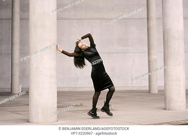 sensitive emotional woman dancing between tall pillars, architecture, fashionable clothes, in city Munich, Germany