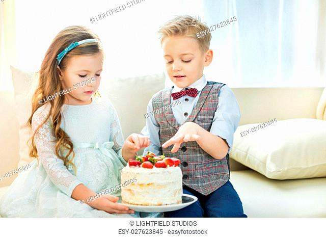 Cute little boy and girl sitting on sofa and holding cake with fresh strawberries