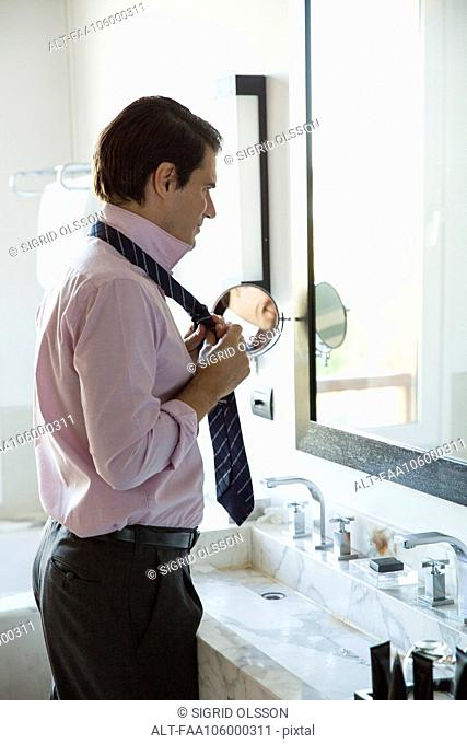 Man getting dressed, adjusting tie in mirror