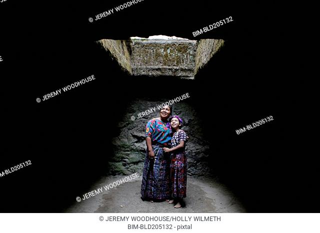 Mother and daughter standing under skylight