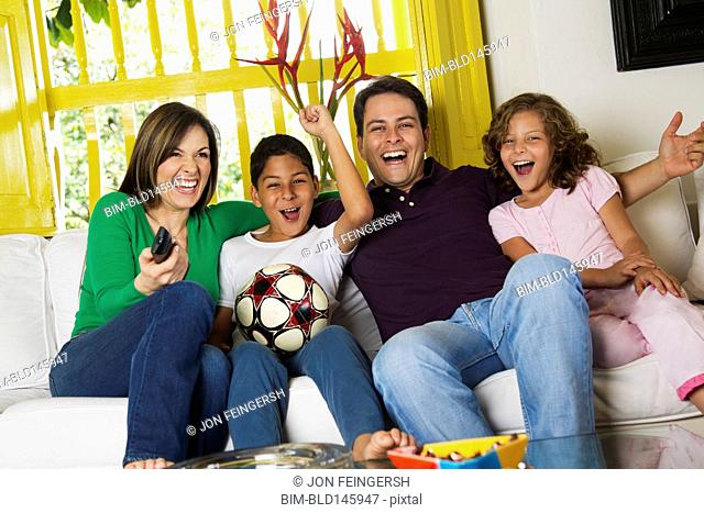 Hispanic family watching soccer on television