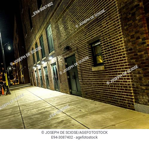 A night scene of a sidewalk and brick wall outside of the Lyric Theatre in Birmingham, Alabama, Dutch angle