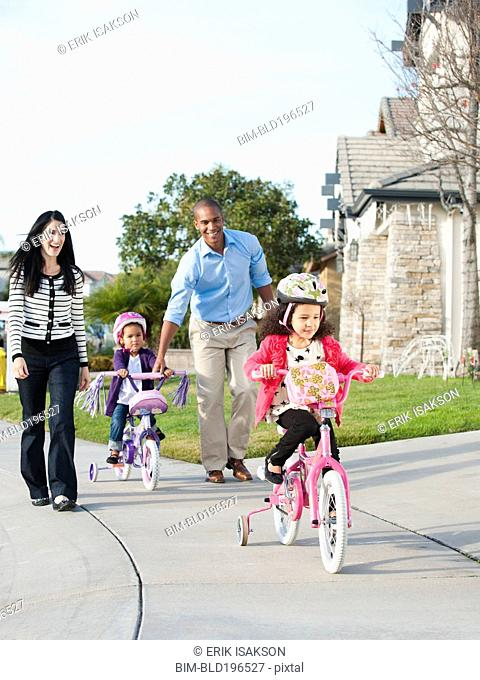 Parents watching children ride bicycles