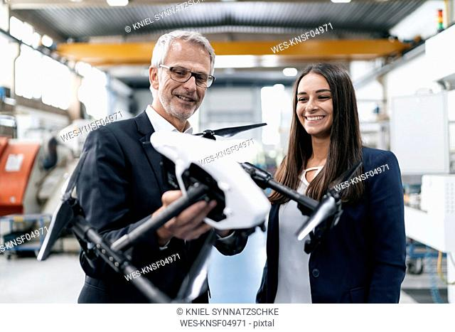 Businessman an woman in high tech enterprise, discussing production of drones