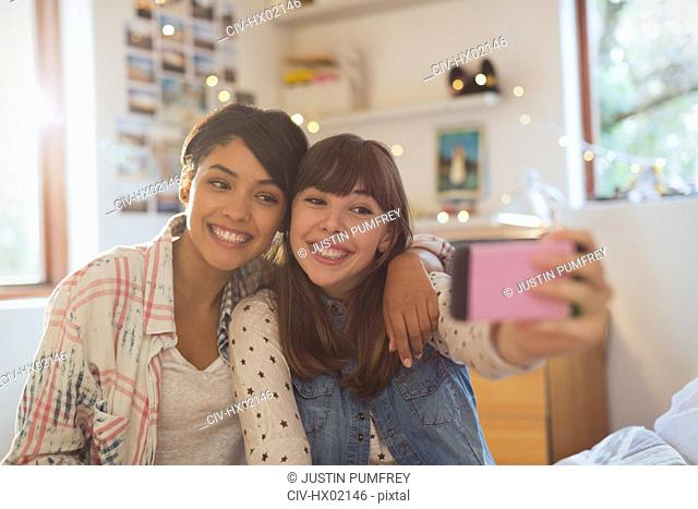 Enthusiastic young women friends taking selfie with camera phone