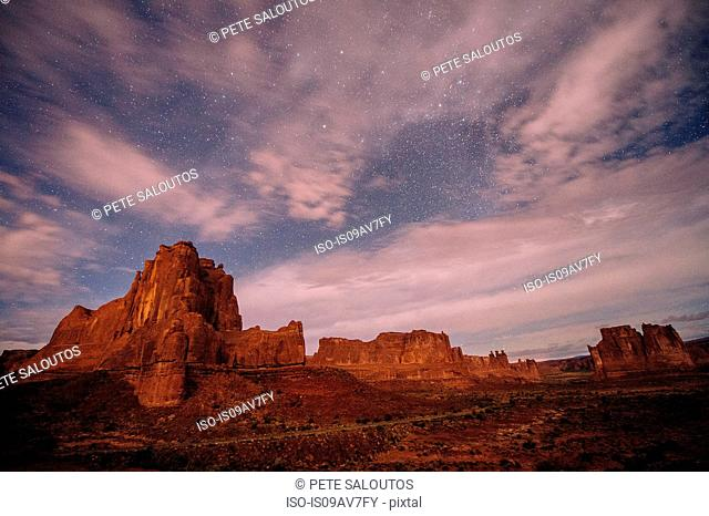 Clouded starry sky and valley rock formations at night, Moab, Utah, USA