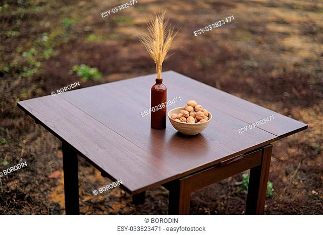 Wooden table with vase and wallnuts standing on the ground closeup