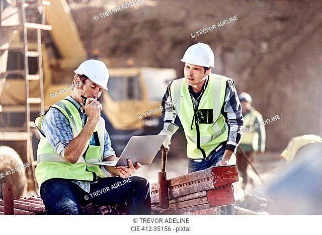 Foreman and construction worker using laptop at construction site