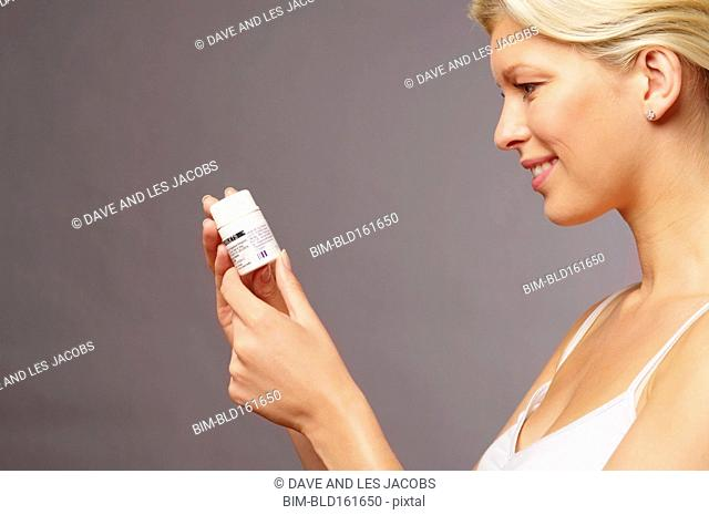 Caucasian woman reading label on medication bottle