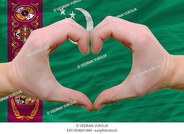 Heart and love gesture showed by hands over flag of turkmenistan