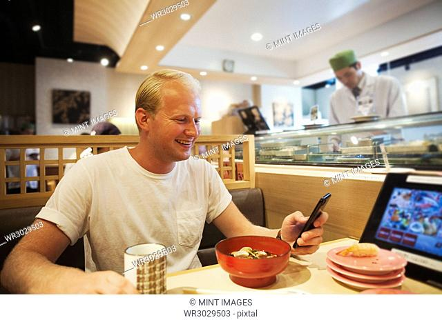 Young man sitting at a table in an Asian Fast Food restaurant, looking at smartphone, smiling