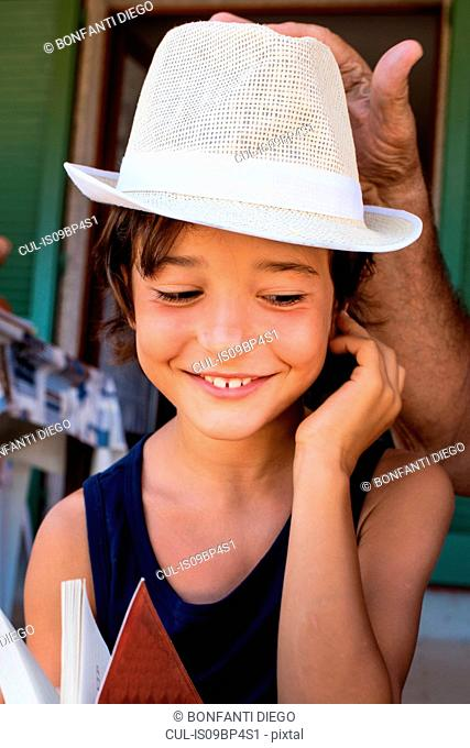 Grandfather placing hat on boy's head