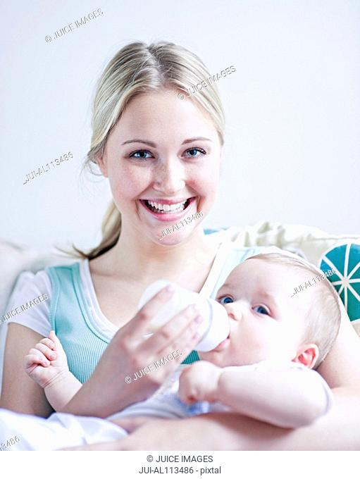 Teenage girl feeding baby boy
